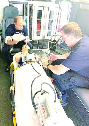 Ken Smith, EMT, and Keith Workman, Paramedic, is working on a practice patient with their new piece of equipment.
